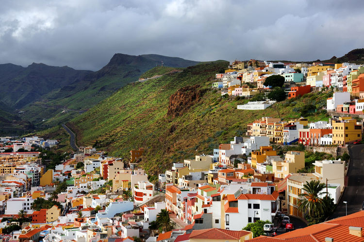 Residential district on mountain at san sebastian de la gomera against cloudy sky