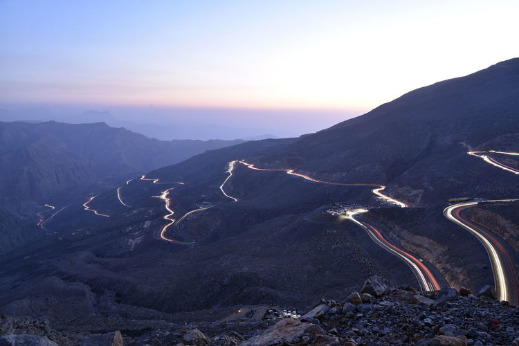 View of light trails on mountain road during dusk