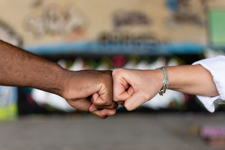 Cropped image of people doing fist bump outdoors