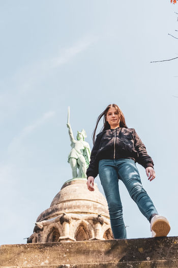 Low angle view of girl standing against sky