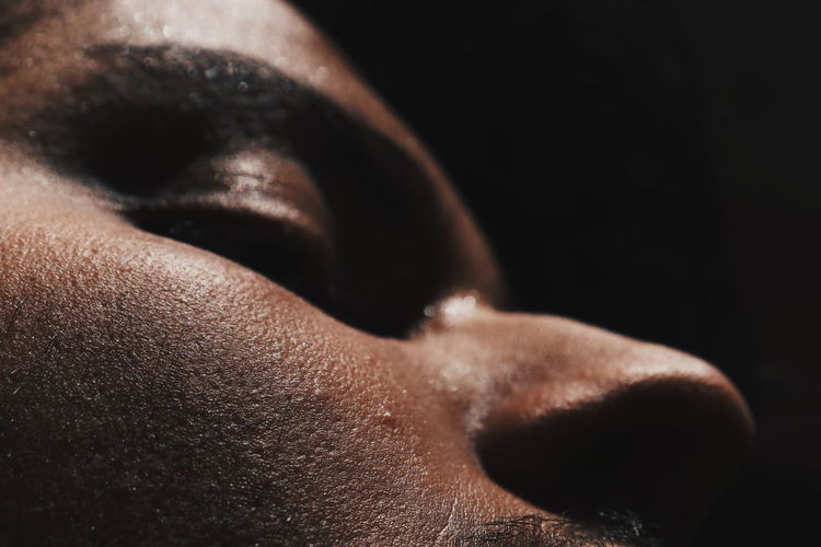 Close-up of man against black background