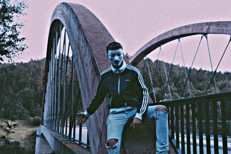 Man standing on footbridge against bridge