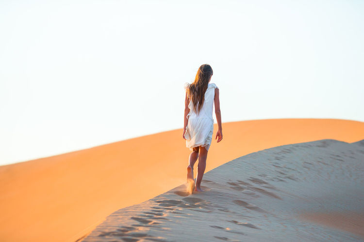 Rear view of girl walking on sand dunes at desert against clear sky