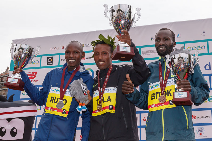 Rome, Italy - April 2, 2017: On stage with the top three finishers in the men's race of the 23rd marathon in Rome. At the center of Tola Shura Kitata first place. To his right, Dominic Ruto Kipngetich, second place. To his left, Bitok Benjamin Kipngetic, third place. Athletes Athletes; Award; Awards Color; Day Ethiopian; Kenyan; Marathon Medal Podium; Rome Marathon Rome Marathon 2017 Rome Marathon 23rd Runners; Winners