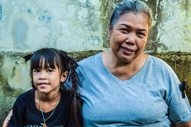 Portrait Of Mother And Daughter Sitting Against Weathered Wall