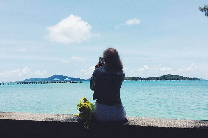 Rear view of woman sitting on retaining wall photographing sea against sky