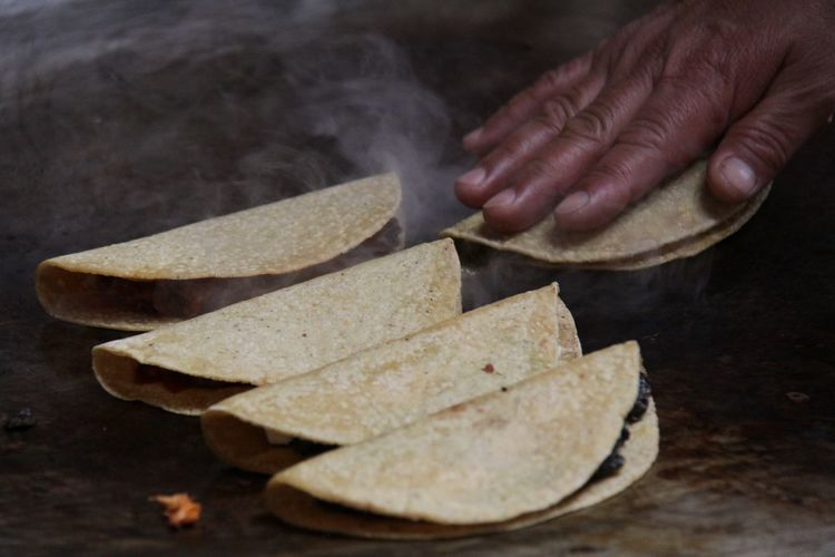 Cropped hand making tacos