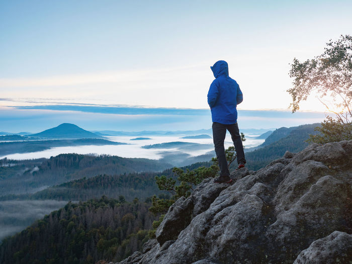 Hiking in sunrise. man hiker wear hood and blue windcheater stay alone in sunset at mountain edge