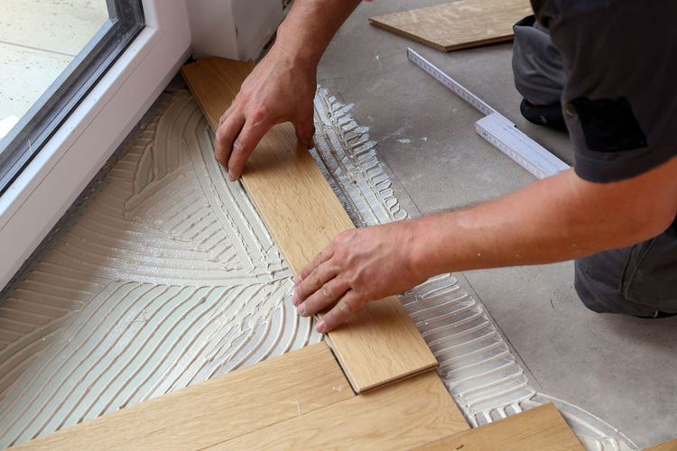 Cropped hands of carpenter placing planks on floor at home