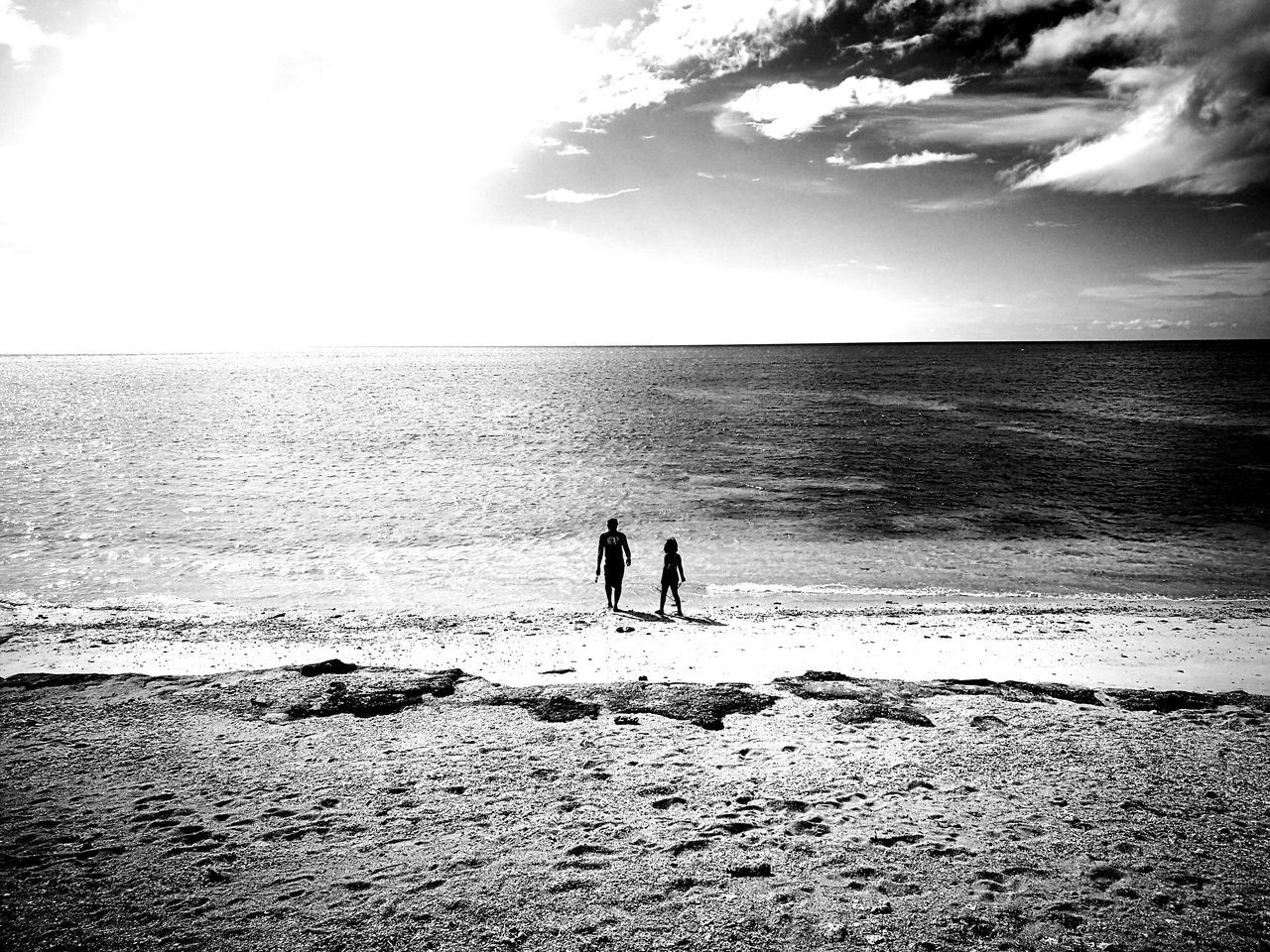 sea, horizon over water, water, beach, togetherness, two people, nature, real people, silhouette, leisure activity, sky, beauty in nature, scenics, men, outdoors, friendship, day, bonding, standing, childhood, people