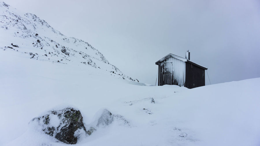 Low Angle View Of House On Snowy Field Against Sky