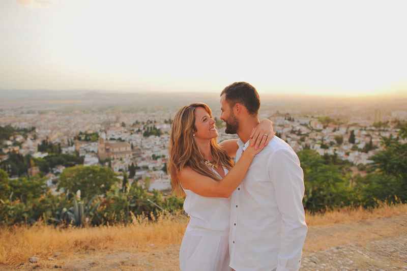 Young couple looking each other face to face while standing in city at sunset