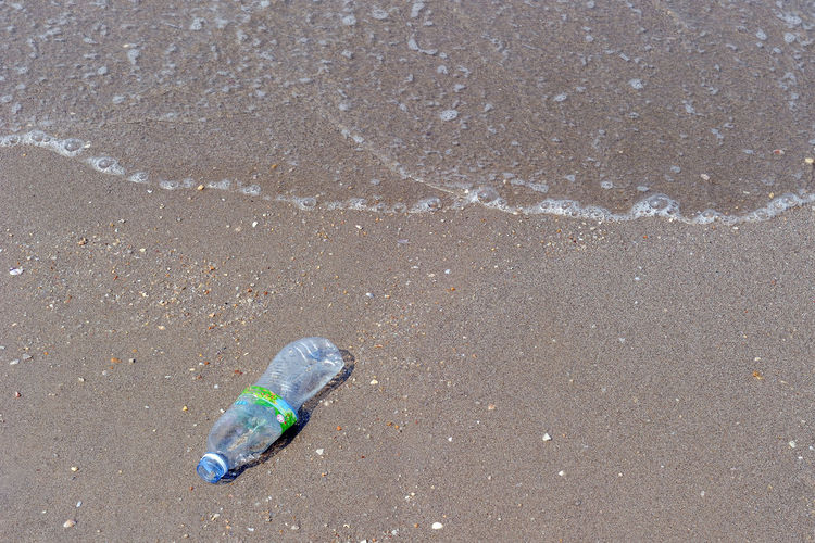Garbage on beach. Plastic Bottle Thoughtlessness Trash Beach Day Dirty Ecology Ecology Problem Environment Garbage High Angle View Landscape Littering Nature No People Not Beautiful Outdoors Sand Sea Water