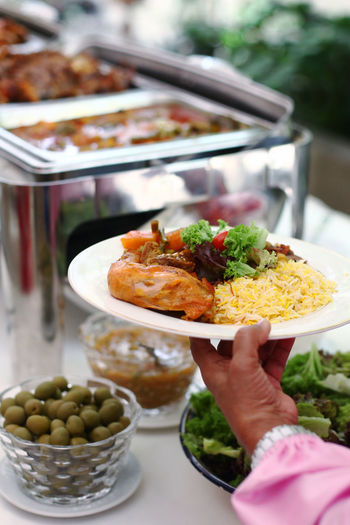 Cropped hand holding food plate