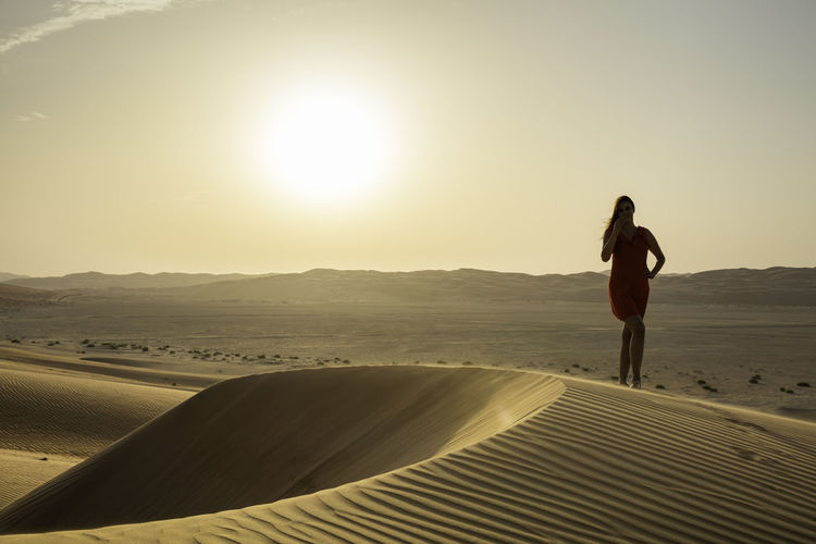 Woman standing at desert against clear sky
