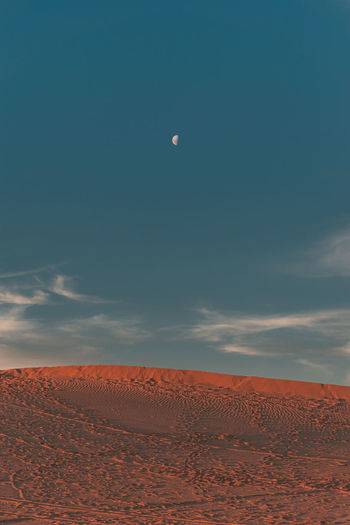 Scenic view of desert against sky and moon