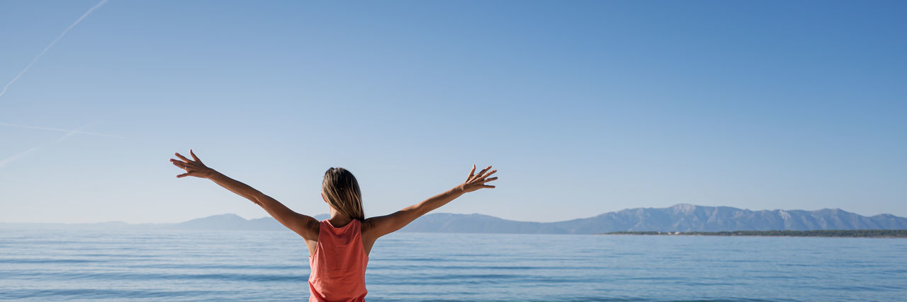 Rear view of woman with arms raised in sea against clear sky