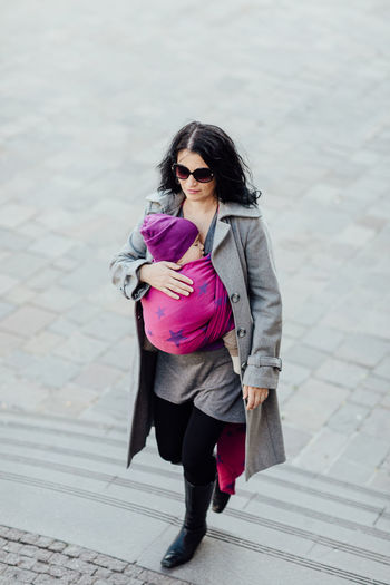 Babywearing mother carrying her child in woven wrap. Portrait of young fashionable woman hugging her sleeping child in sling. Baby Babywearing Motherhood Carry Carrier Wrap Sling Child Infant Wear Attachment Parenting Woman Relationship Bonding Closeness Togetherness Together Woven Caucasian Love Ergonomic City Safety Full Length