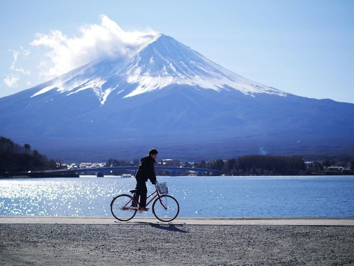 Man riding bicycle by river against mountain and sky