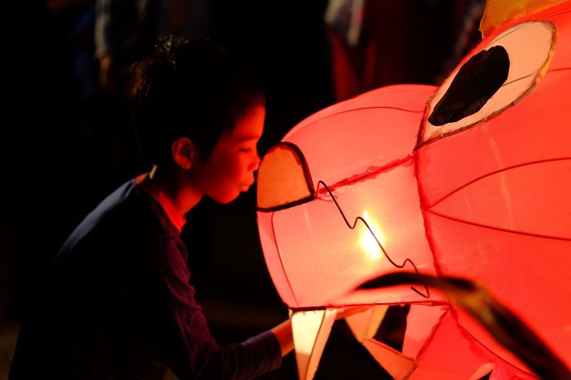 Close-Up Of Boy Looking At Illuminated Lantern At Night