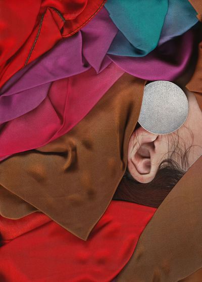 Cropped ear of person amidst colorful fabrics