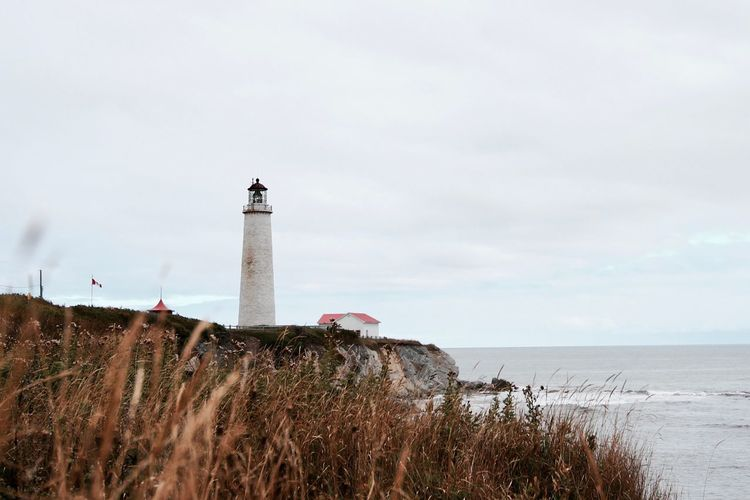 Moody lighthouse Lighthouse Beach Sky History Building Exterior Grass Outdoors Nature Water Sea Travel Destinations Architecture Tranquility Moody Moody Weather Focus Blurry Building Tall White Cloud - Sky Horizon Over Water Fall Automn