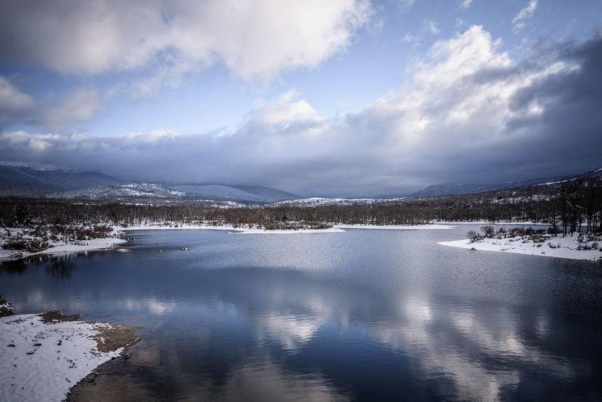 A panoramic view of a winter landscape of a snow-covered lake and mountain. Landscape_Collection Panoramic Reflection SPAIN Tranquility Water Reflections Winter Wintertime Beauty Blue Sky Clouds Clouds And Sky Day Lake Lake View Landscape Landscape_photography Mountain Mountais And Lake Reflections In The Water Sky Sunset Water Wide Angle Winter Trees Shades Of Winter