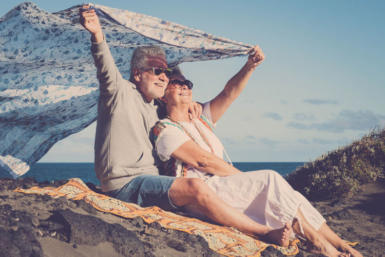 Senior Couple Holding Scarf While Relaxing At Beach