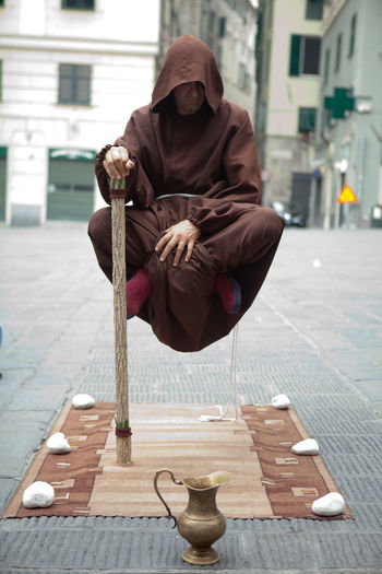 View Of Hooded Man Levitating Above Street