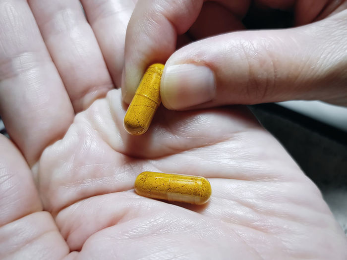 Cropped hand holding capsules
