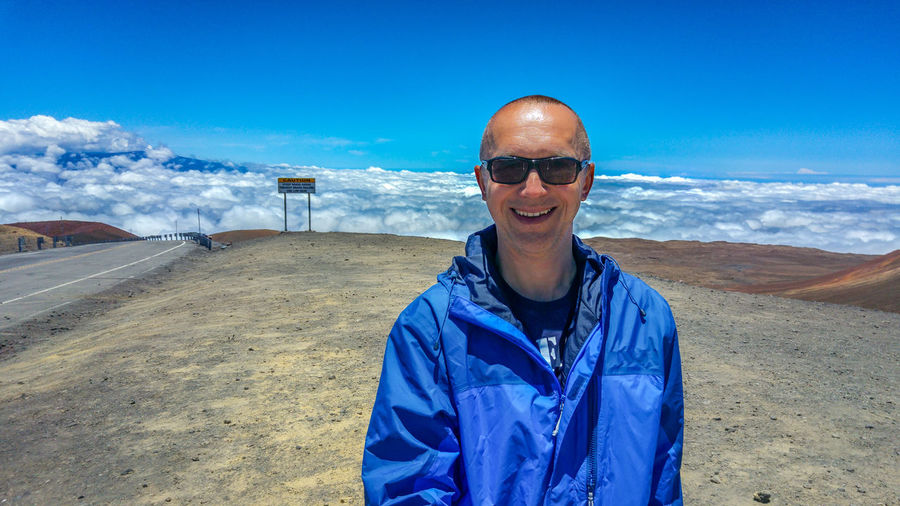 Smiling Man Wearing Sunglasses While Standing On Mountain Against Sky At Mauna Kea