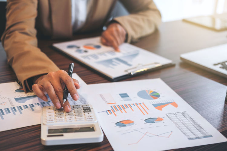 Midsection Of Businessman Using Calculator While Analyzing Graphs