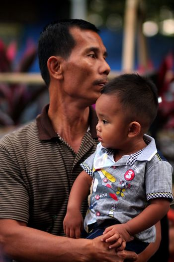 Father Carrying Son Looking Away While Standing Outdoors
