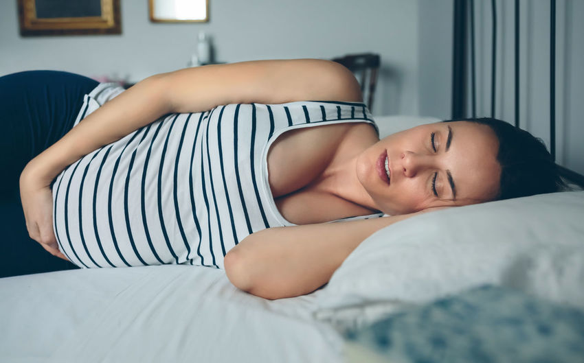 Pregnant woman sleeping on her side in bed Bed Care Embraced Hands Horizontal Love Lying Mother Motherhood Relaxing Wait Woman Bedroom Belly Caucasian Expectation Female Girl Holding Maternal Mom Pregnancy Pregnant Sleeping Tummy