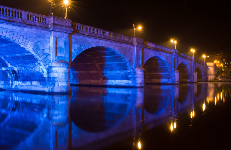 Reflection of illuminated bridge in water