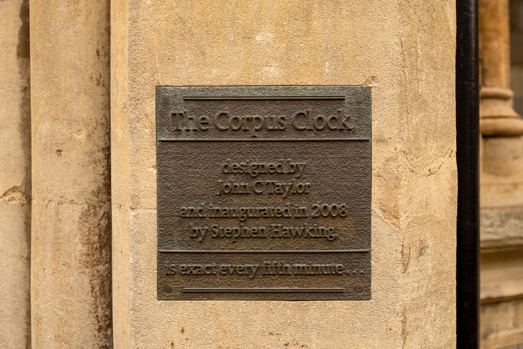 A bronze plaque embedded in a lime stone wall for the Corpus Clock in Cambridge, UK. Cambridge Cambridgeshire John C Taylor University City Brass Brass Plaque Clock Designed By Designer  Limestone Plaque Stephen Hawking The Corpus Clock Time Piece Text History The Past Architecture Craft Close-up Carving - Craft Product No People Communication Art And Craft Ancient Tombstone Marble Script Non-western Script Travel Destinations Built Structure Ancient Civilization Western Script Religion Engraved Image Archaeology