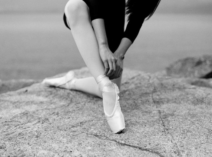 Midsection of ballerina tying shoe on rock