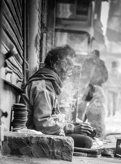 Shoeshiner working while sitting amidst smoke on sidewalk in city