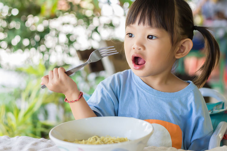 Portrait of cute girl holding fork by table