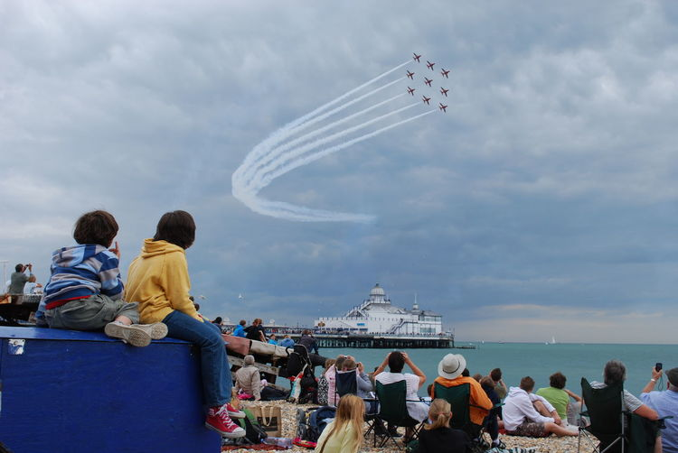 Red Arrows fly over children and crowds at Eastbourne Pier and beach Airshow Arts Culture And Entertainment British Seaside Airshow Children Watching Red Arrows At Eastbourne Pier Cloud - Sky Eastbourne Airbourne Eastbourne Pier Airshow Enjoyment Fun Large Group Of People Leisure Activity Lifestyles Mixed Age Range Outdoors Red Arrows Air Display Red Arrows At Eastbourne Seaside Red Arrows Eastbourne Coast Red Arrows Flying Over Eastbourne Pier Sky Tourism Tourist Travel Destinations Vacations