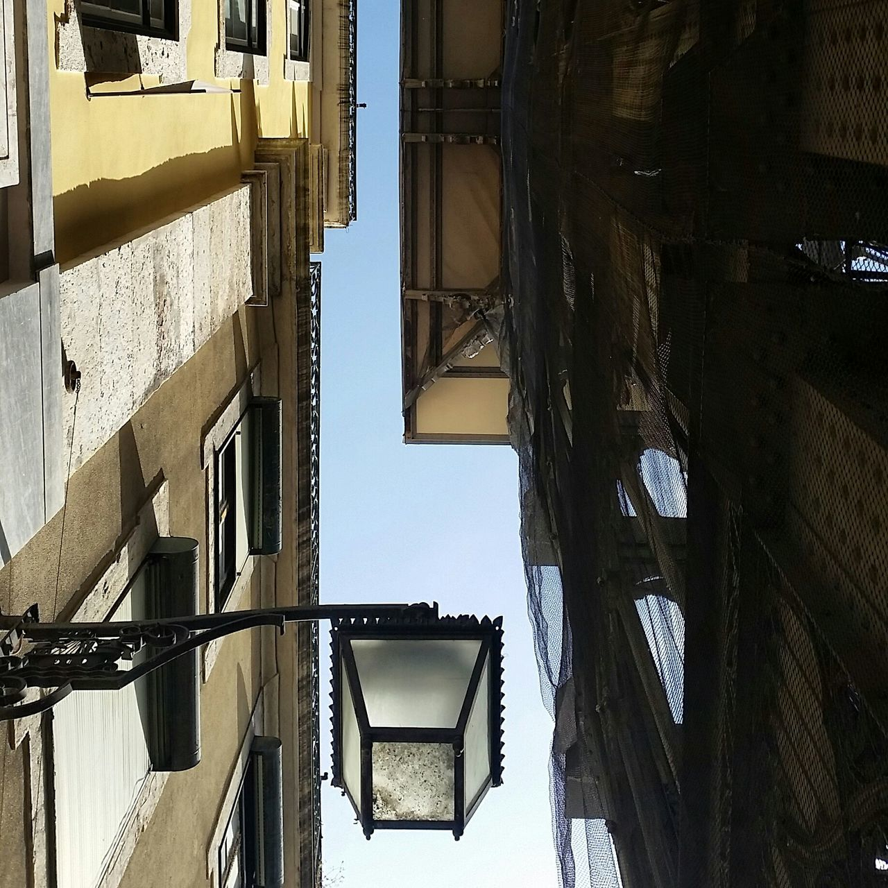 Directly Below Shot Of Street Light And Buildings Against Clear Sky