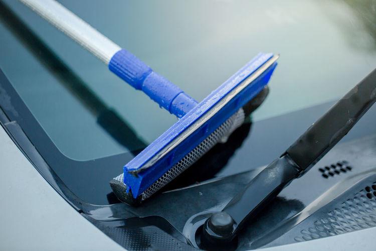 Close-up of squeegee over car windshield
