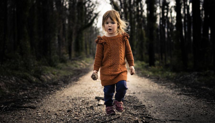 Full length of girl walking on road in forest