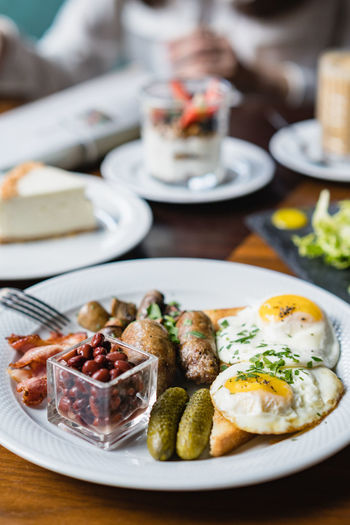 full English breakfast served on a table Food And Drink English Breakfast Food Plate Freshness Breakfast High Angle View Close-up Serving Size No People Vegetable Ready-to-eat Wellbeing Still Life Healthy Eating Eggs Cucumbers Focus On Foreground Drink Table Delicious Food Yummy Meal Egg Glass Meat Gastronomy Food And Drink Breakfast Time Indoors  Beans Brunch Time Brunch Meal Dish Served Morning Breakfast Roasted Fresh Food Green Color Yummy :) Food Porn Foodphotography British Culture