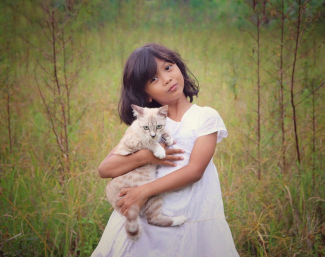Portrait of cute girl holding cat against while standing on field