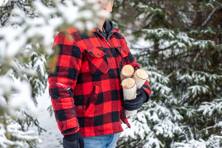 Midsection of person standing by tree during winter