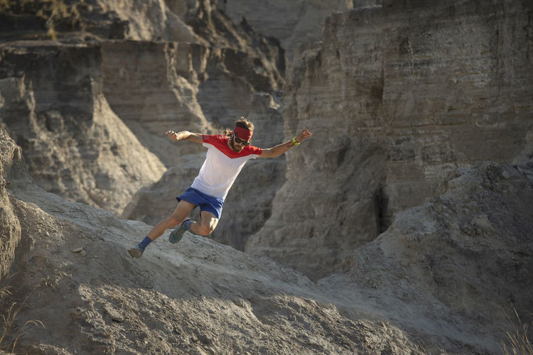 Rear view of person jumping on rock