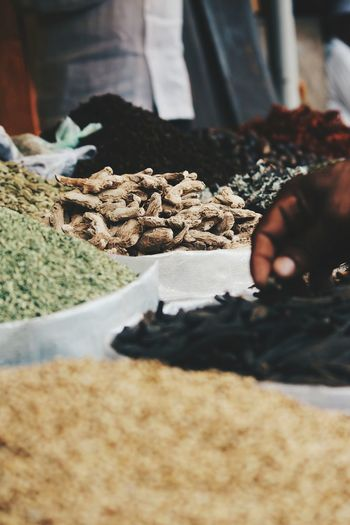 Cropped hand holding spice at market stall