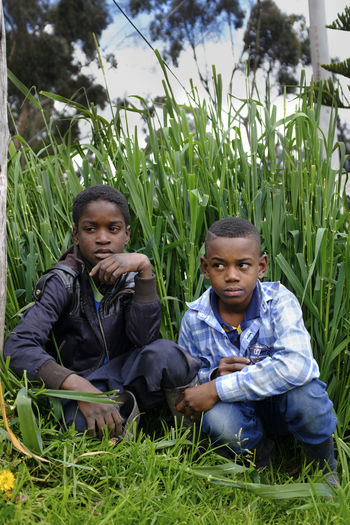 Jose and Edinson, 11 years old, hang out outside on a sunday, San Germán is a slum on the outskirts of Bogotá, where vulnerable populations including victims of the armed conflict, ex-guerilla members, single mothers, indigenous and afro communities this neighborhood land is under constant dispute and violence is people here are resilient and determined to stand tall. Bogotá Colombia Displacement Boat War Memorial Field Green Color Inequality Informality Land Leisure Activity Lifestyles Men Nature Outdoors People Real People Slum Area War