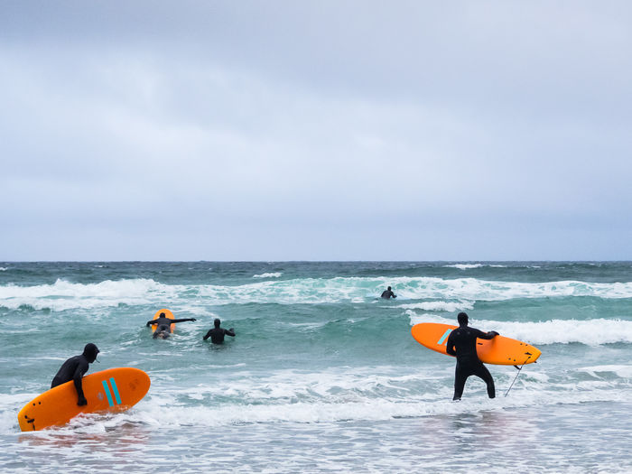 Male surfers surfing in sea against sky
